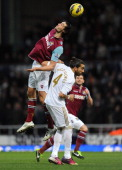 Andy Carroll of West Ham United wins a header from Chico Flores of Swansea City during the Barclays Premier League match between West Ham United and...