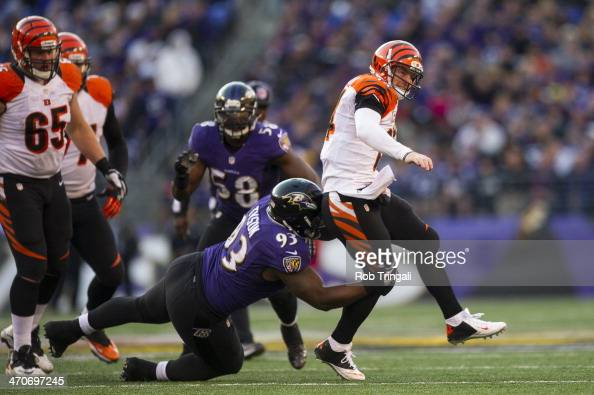 Andy Dalton of the Cincinnati Bengals drops back to avoid a tackle by DeAngelo Tyson of the Baltimore Ravens during the game between the two teams at...