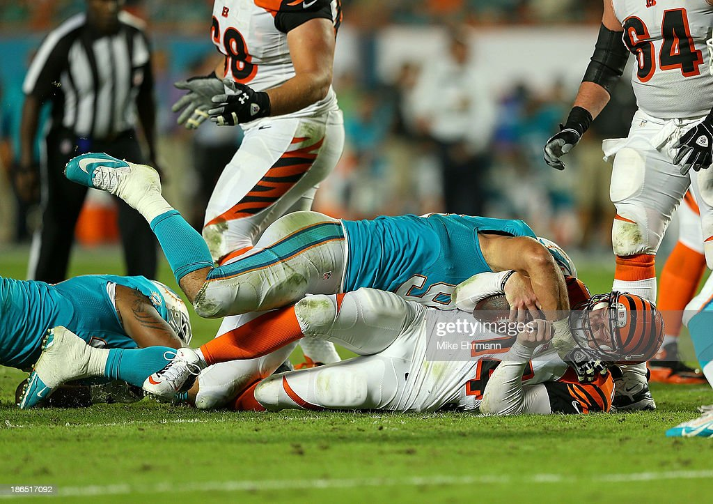 Andy Dalton #14 of the Cincinnati Bengals is sacked during a game against the Miami Dolphins at Sun Life Stadium on October 31, 2013 in Miami Gardens, Florida.