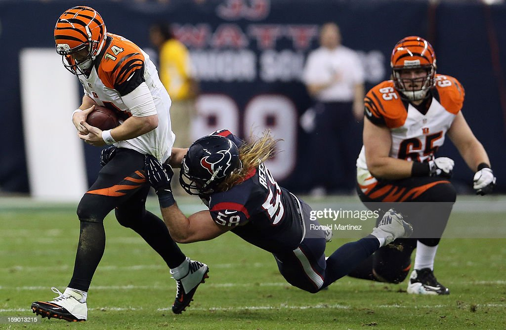 Andy Dalton #14 of the Cincinnati Bengals is tackled by Brooks Reed #58 of the Houston Texans during the AFC Wild Card Playoff Game at Reliant Stadium on January 5, 2013 in Houston, Texas.
