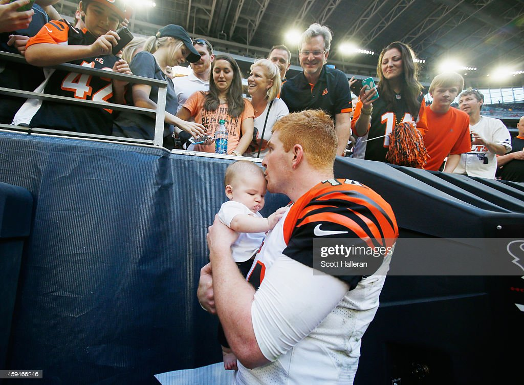 Andy Dalton of the Cincinnati Bengals kisses his son Noah in front of his family and fans in the stands after the Bengals defeated the Houston Texans...