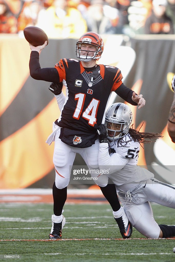 Andy Dalton #14 of the Cincinnati Bengals passes the ball upfield against the pressure of Phillip Wheeler #52 of the Oakland Raiders during their game at Paul Brown Stadium on November 25, 2012 in Cincinnati, Ohio. The Bengals defeated the Raiders 34-10.