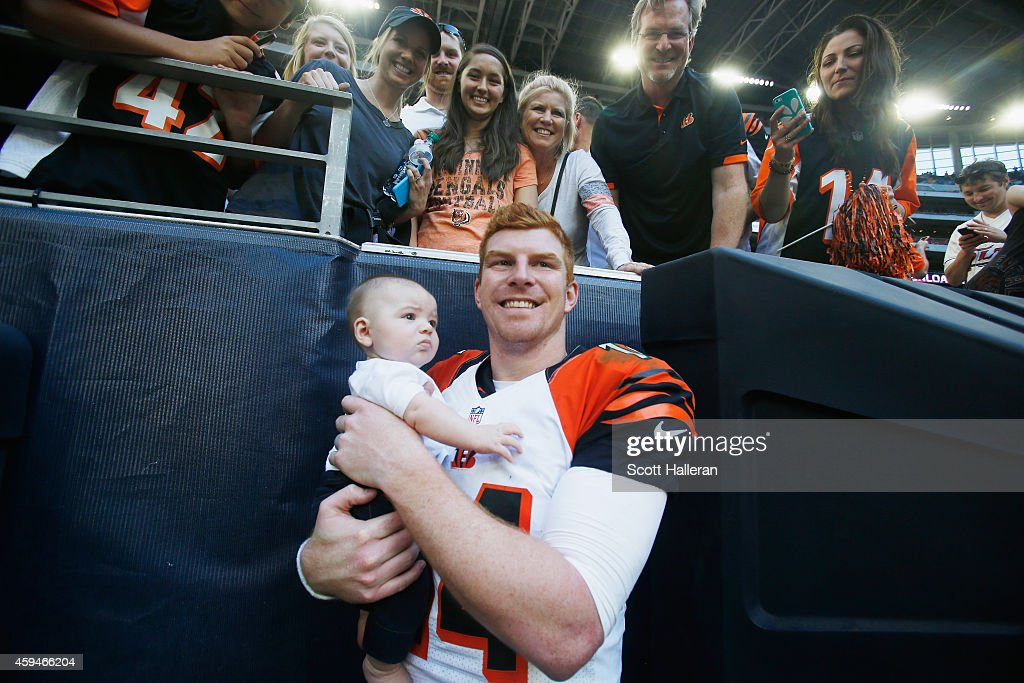Andy Dalton of the Cincinnati Bengals poses with his son Noah in of his family and fans in the stands after the Bengals defeated the Houston Texans...