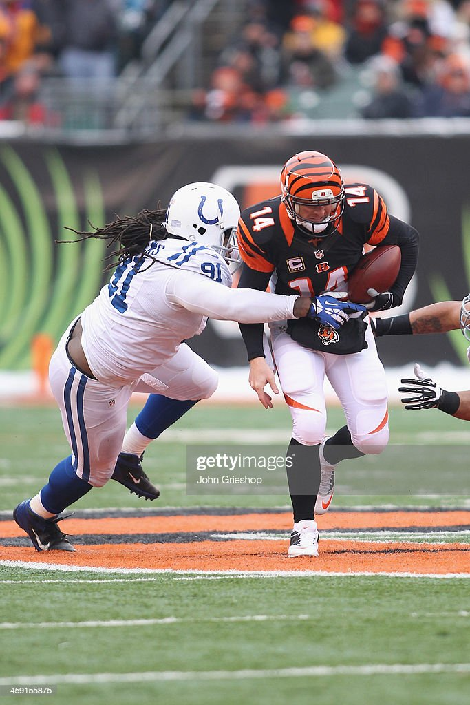 Andy Dalton of the Cincinnati Bengals runs the ball upfield against the pressure of Ricardo Matthews of the Indianapolis Colts during their game at...