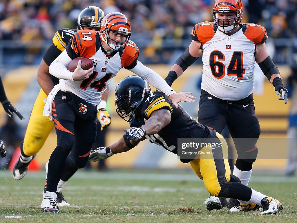 Andy Dalton #14 of the Cincinnati Bengals tries to get around the tackle of James Harrison #92 of the Pittsburgh Steelers during the fourth quarter at Heinz Field on December 23, 2012 in Pittsburgh, Pennsylvania. Cincinnati won the game 13-10.