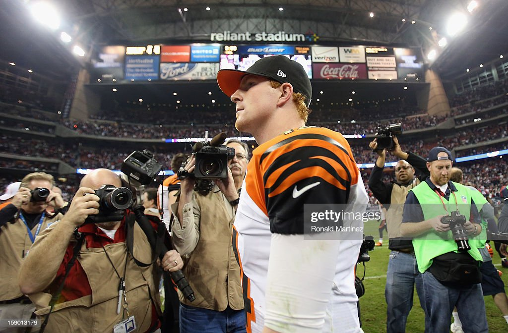 Andy Dalton #14 of the Cincinnati Bengals walks off the field after a 13-19 loss against the Houston Texans during the AFC Wild Card Playoff Game at Reliant Stadium on January 5, 2013 in Houston, Texas.