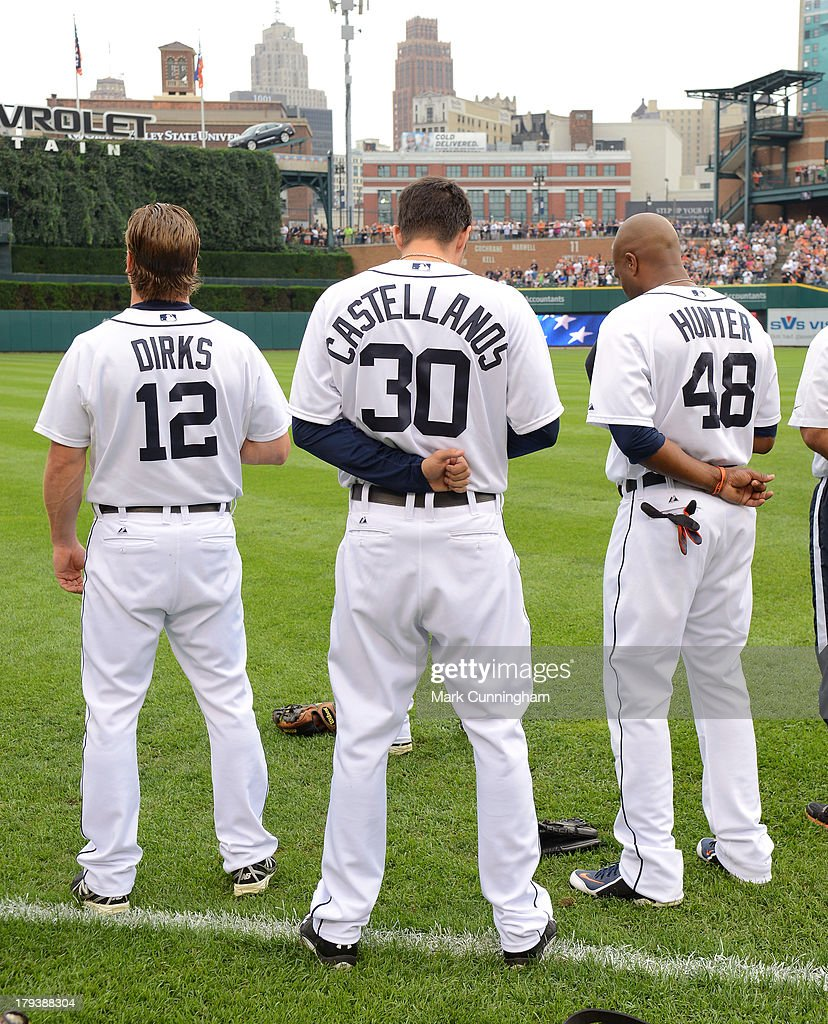 Andy Dirks #12, Nick Castellanos #30 and Torii Hunter #48 of the Detroit Tigers stand together on the field during the National Anthem prior to the game against the Cleveland Indians at Comerica Park on September 1, 2013 in Detroit, Michigan. The Indians defeated the Tigers 4-0.