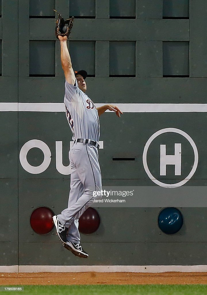 Andy Dirks #12 of the Detroit Tigers catches a fly ball at the wall against the Boston Red Sox during the game on September 4, 2013 at Fenway Park in Boston, Massachusetts.