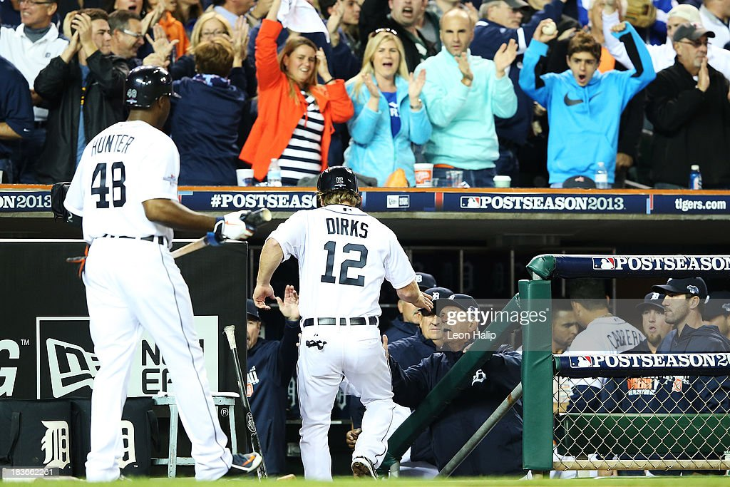 Andy Dirks #12 of the Detroit Tigers celebrates with teammates in the dugout after scoring on a single by Jose Iglesias #1 in the seventh inning against the Oakland Athletics during Game Four of the American League Division Series at Comerica Park on October 8, 2013 in Detroit, Michigan.