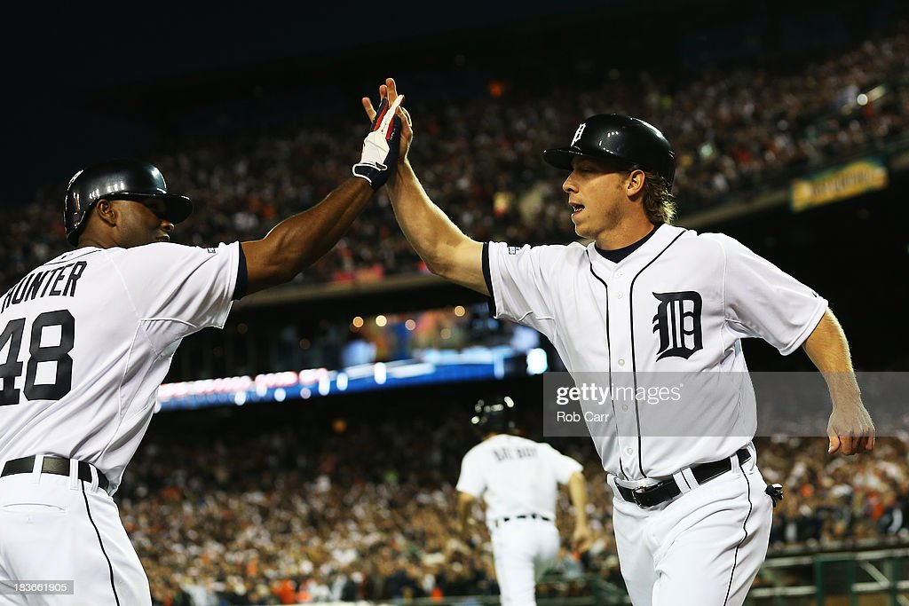 Andy Dirks #12 of the Detroit Tigers celebrates with Torii Hunter #48 after scoring on a single by Jose Iglesias #1 in the seventh inning against the Oakland Athletics during Game Four of the American League Division Series at Comerica Park on October 8, 2013 in Detroit, Michigan.