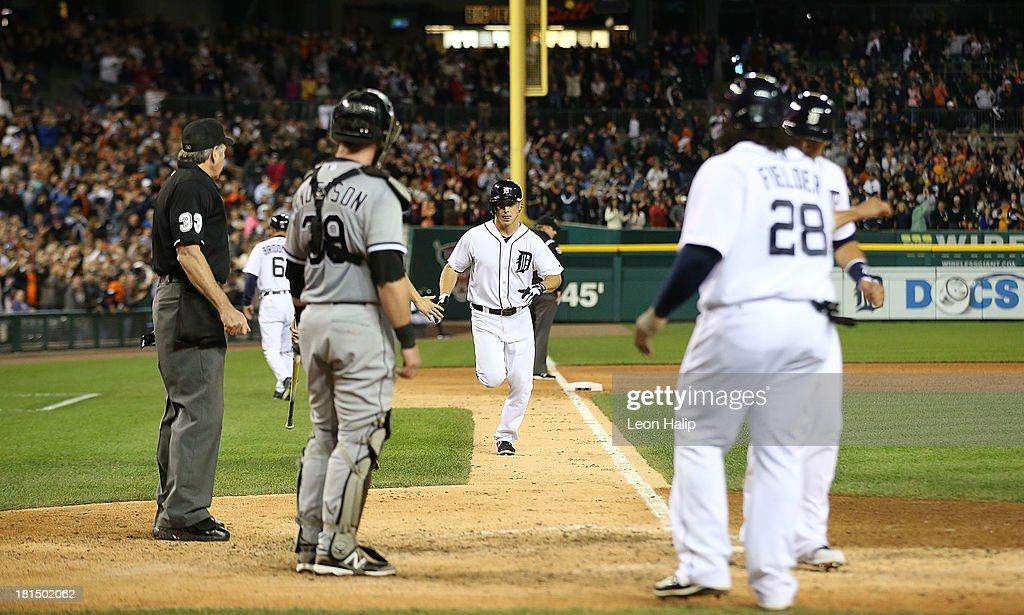 Andy Dirks #12 of the Detroit Tigers rounds third base after hitting a three run home run in the ninth inning scoring Prince Fielder #28 and Victor Martinez #41 during the game against the Chicago White Sox at Comerica Park on September 21, 2013 in Detroit, Michigan.