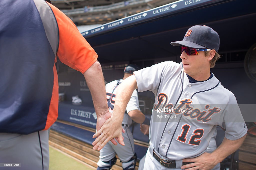 Andy Dirks #12 of the Detroit Tigers slaps five in the dugout during the game against the New York Yankees at Yankee Stadium on August 11, 2013 in the Bronx borough of Manhattan.