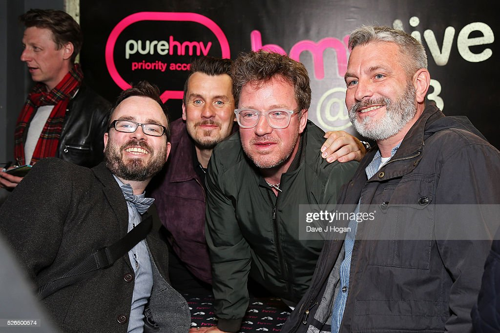 Andy Dunlop (2L) and Neil Primrose (2R) of Travis pose for photos with fans after performing songs from the new album 'Everything At Once' at HMV Oxford Street on April 30, 2016 in London, England.