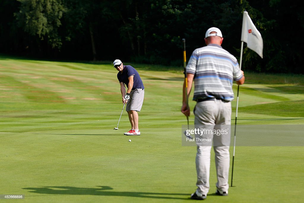 Andy Dyble (L) of Pennant Park Golf Club putts while being watched by team mate Andrew Barnett during The Lombard Trophy North West Regional Qualifier at Dunham Forest Golf Club on July 25, 2014 in Altrincham, England.