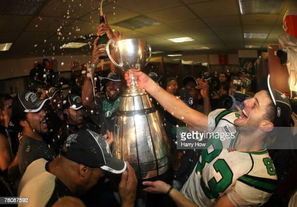 Andy Fantuz of the Saskatchewan Rough Riders hoist the trophy amongst champagne in celebration of a victory over the Winnipeg Blue Bombers during the...
