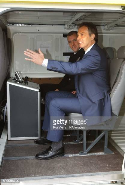 PC Andy Ferguson shows Britain's Prime Minister Tony Blair the inside of a surveillance mobile video unit van during a visit to Whitefield Police...