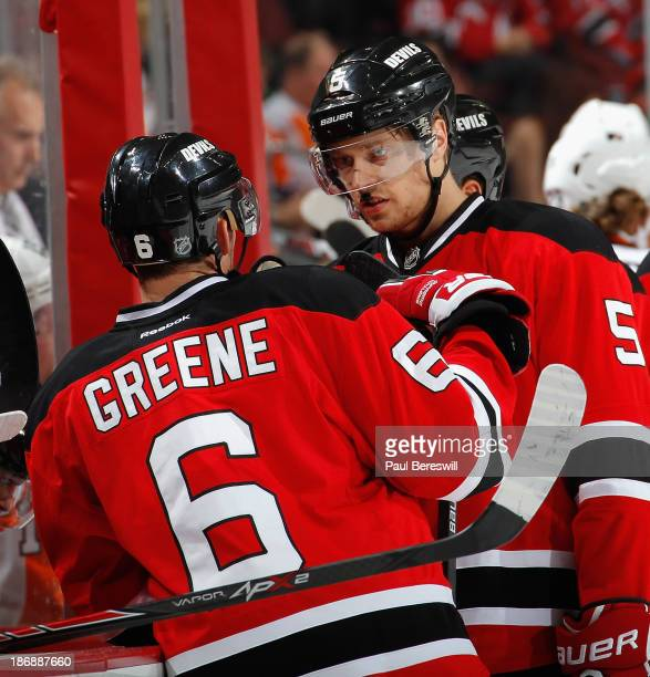 Andy Greene and Adam Larsson of the New Jersey Devils talk during a break in the action in an NHL hockey game against the Philadelphia Flyers at...