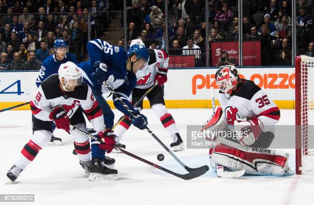 Andy Greene of the New Jersey Devils and teammate goalie Cory Schneider skate against James van Riemsdyk of the Toronto Maple Leafs during the first...
