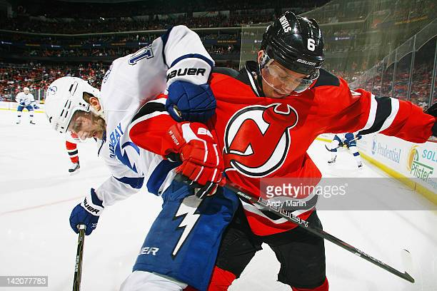 Andy Greene of the New Jersey Devils and Tom Pyatt of the Tampa Bay Lightning battle in thr corner during the game at the Prudential Center on March...