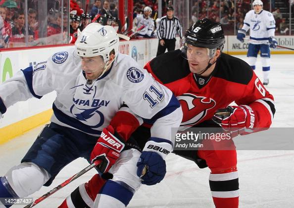 Andy Greene of the New Jersey Devils and Tom Pyatt of the Tampa Bay Lightning skate for position during the game at the Prudential Center on March 29...