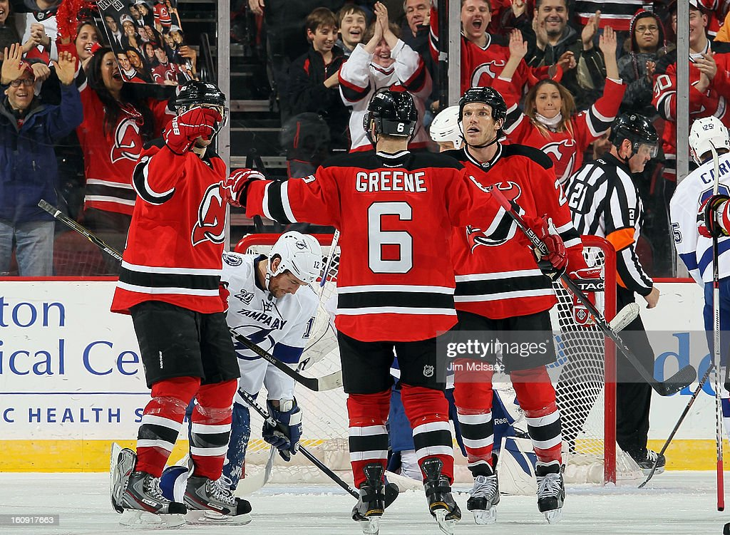 Andy Greene #6 of the New Jersey Devils celebrates after scoring a third period power play goal against the Tampa Bay Lightning with teammates David Clarkson #23 and Travis Zajac #19 at the Prudential Center on February 7, 2013 in Newark, New Jersey.