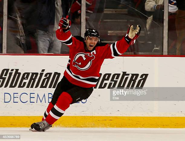 Andy Greene of the New Jersey Devils celebrates his teammate's game winning goal in overtime against the Buffalo Sabres at Prudential Center on...