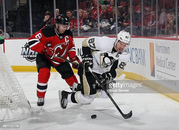 Andy Greene of the New Jersey Devils checks Sidney Crosby of the Pittsburgh Penguins during the first period at the Prudential Center on November 14...