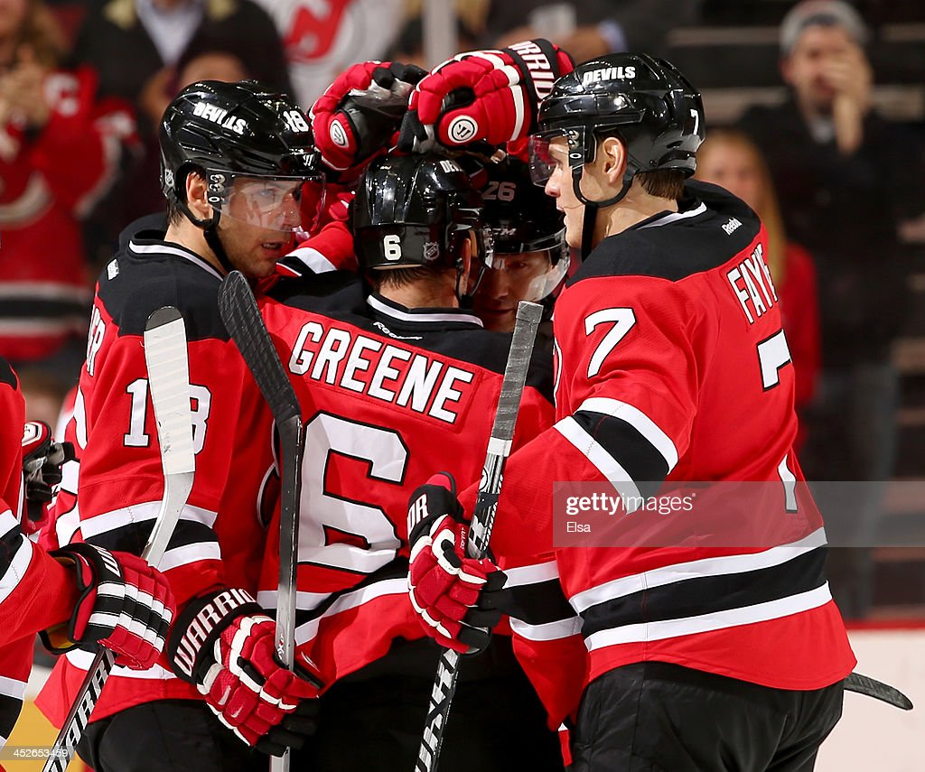 Andy Greene #6 of the New Jersey Devils is congratulated by teammates Steve Bernier #18,Patrik Elias #26 and Mark Fayne #7 after Greene scored against the Carolina Hurricanes at Prudential Center on November 27, 2013 in Newark, New Jersey.The Carolina Hurricanes defeated the New Jersey Devils 4-3.