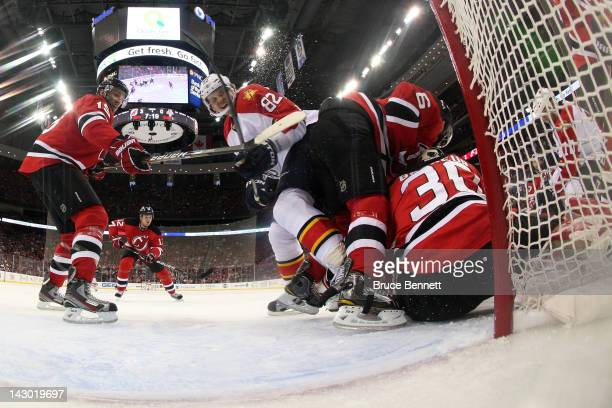 Andy Greene of the New Jersey Devils skates into his teammate goalie Martin Brodeur in the first period against Tomas Kopecky of the Florida Panthers...