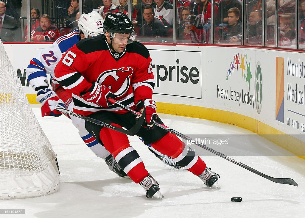 Andy Greene #6 of the New Jersey Devils tries to keep the puck from Brian Boyle #22 of the New York Rangers at the Prudential Center on March 19, 2013 in Newark, New Jersey. The New York Rangers defeated the New Jersey Devils 3-2.