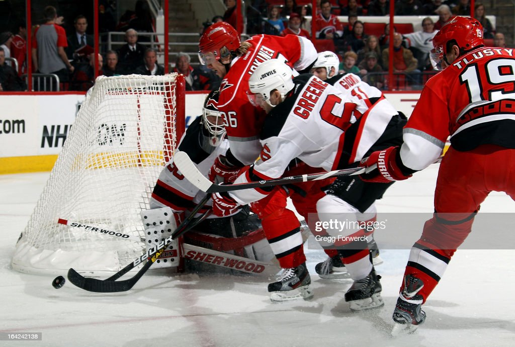 Andy Greene #6 of the New Jersey Devils tries to prevent Jussi Jokinen #36 of the Carolina Hurricanes from getting to a loose puck as Martin Brodeur #30 protects the goal during their NHL game at PNC Arena on March 21, 2013 in Raleigh, North Carolina.