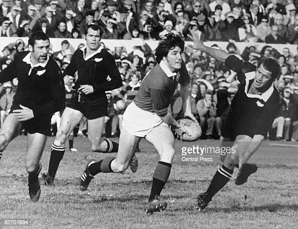 Andy Irvine of the British Lions evades a tackle by Kevin Eveleigh of the New Zealand All Blacks during the second rugby test match at Christchurch...