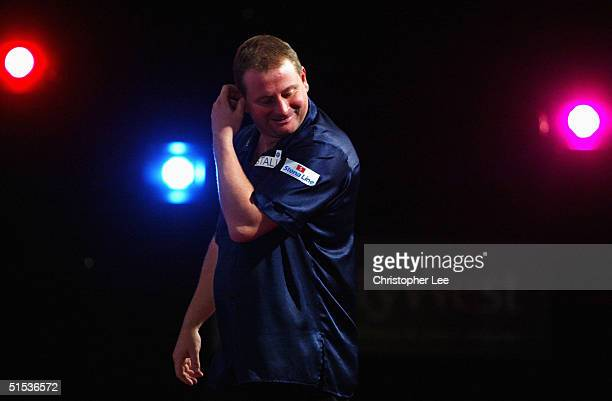Andy Jenkins of England looks dejected as he loses to Alan Warriner of England during their 2004 Skybet World Darts Grand Prix Second Round on...