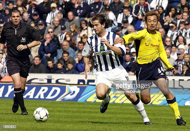 Andy Johnson of West Bromwich Albion takes the ball past Kazuyuki Toda of Tottenham Hotspur during the FA Barclaycard Premiership match between West...