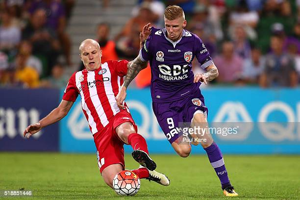 Andy Keogh of the Glory is challenged by Aaron Mooy of Melbourne during the round 26 ALeague match between the Perth Glory and Melbourne City FC at...