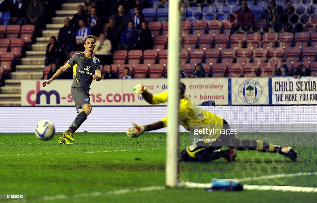 Andy King of Leicester City shoots past Ali Al Habsi of Wigan Athletic to score during the Sky Bet Championship match between Wigan Athletic and Leicester City at DW Stadium on April 01, 2014 in Wigan, England.