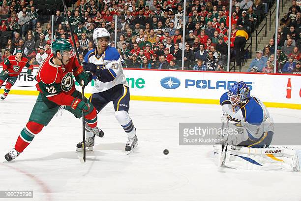 Andy McDonald and goalie Brian Elliott of the St Louis Blues defend against Cal Clutterbuck of the Minnesota Wild during the game on April 1 2013 at...
