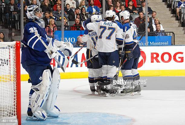 Andy McDonald Jay McKee and Roman Polak of the St Louis Blues celebrate with teammates as goaltender Vesa Toskala of the Toronto Maple Leafs looks on...