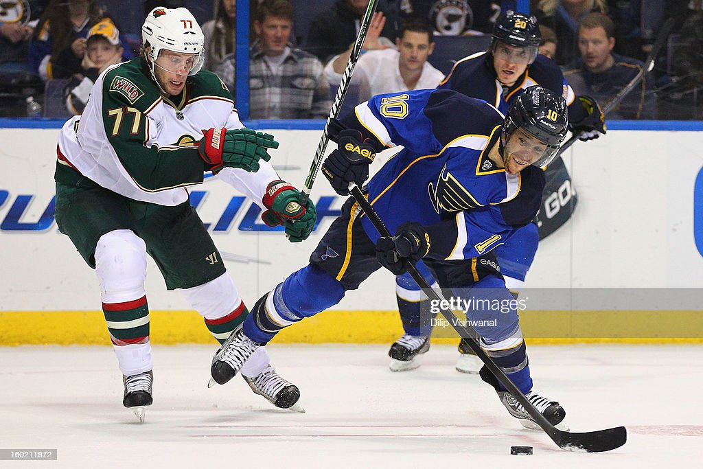 Andy McDonald #10 of the St. Louis Blues looks to pass the puck against <a gi-track='captionPersonalityLinkClicked' href=/galleries/search?phrase=Tom+Gilbert&family=editorial&specificpeople=687083 ng-click='$event.stopPropagation()'>Tom Gilbert</a> #77 of the Minnesota Wild at the Scottrade Center on January 27, 2013 in St. Louis, Missouri. The Blues beat the Wild 5-4 in overtime.