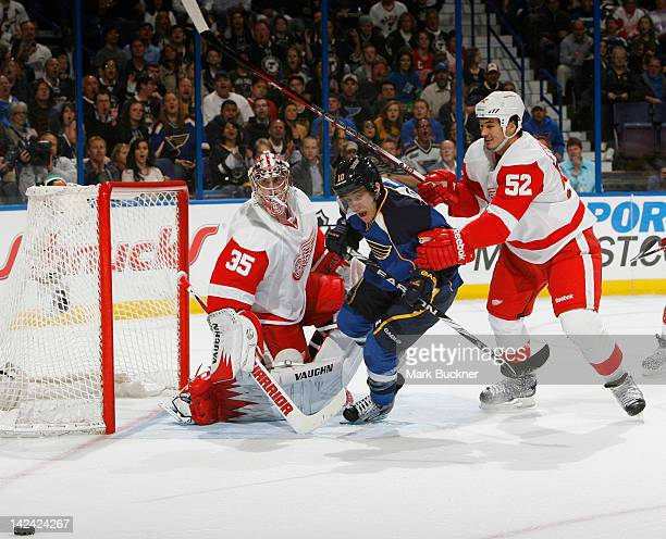 Andy McDonald of the St Louis Blues skates between goalie Jimmy Howard and Jonathan Ericsson of the Detroit Red Wings in an NHL game on April 4 2012...