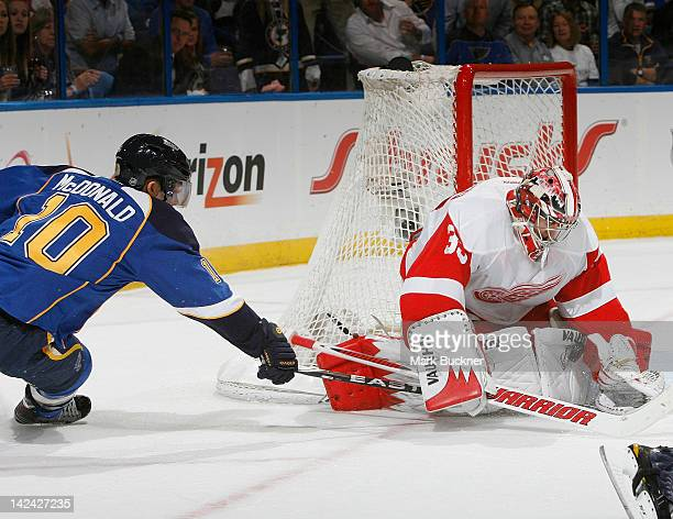 Andy McDonald of the St Louis Blues tries to poke the puck past goalie Jimmy Howard of the Detroit Red Wings in an NHL game on April 4 2012 at...