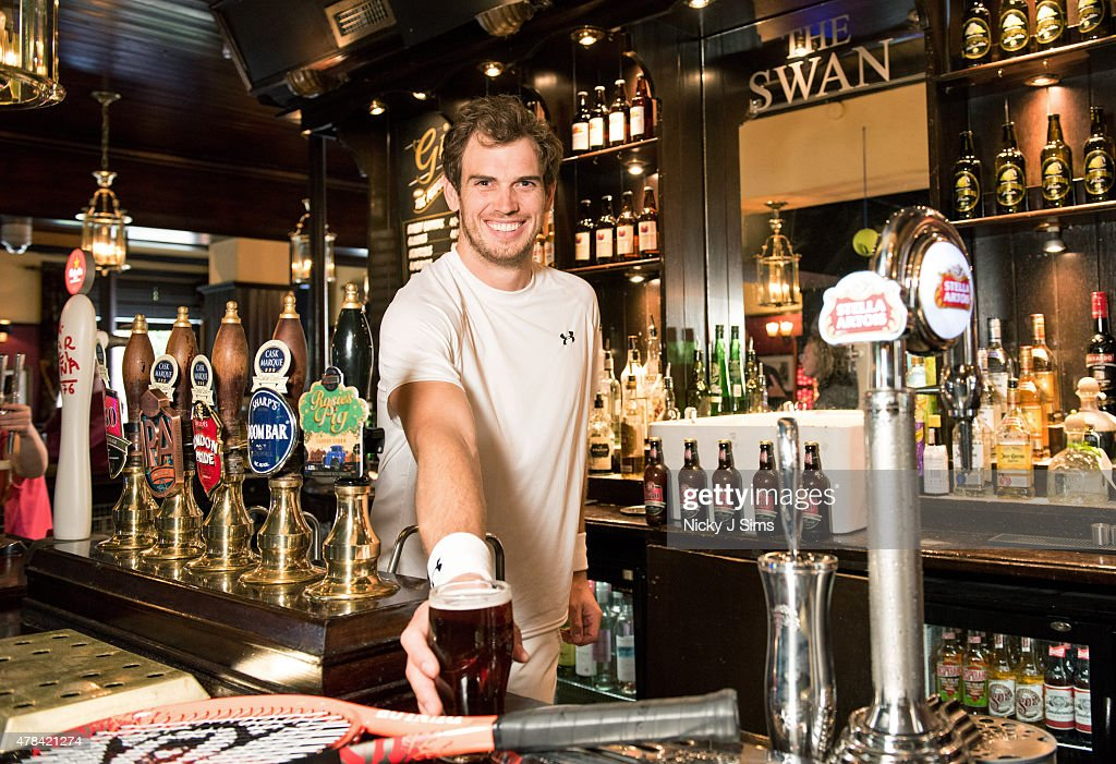 Andy Murray lookalike Scott Millar tries out his skills at pouring a pint at Wimbeldon's The Swan Pub on June 23, 2015 in London, England.