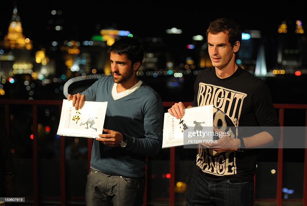 Andy Murray of Britain (R) and Janko Tipsarevic of Serbia (L) show traditional Chinese paper cuttings they did on a rooftop overlooking the Bund, at a sponsors event ahead of the Shanghai Masters tennis tournament in Shanghai, on October 7, 2012. Murray can build on his breakthrough year by becoming the number one player in the world, top-ranked Swiss rival Roger Federer said at an earlier press conference. AFP PHOTO/Peter PARKS