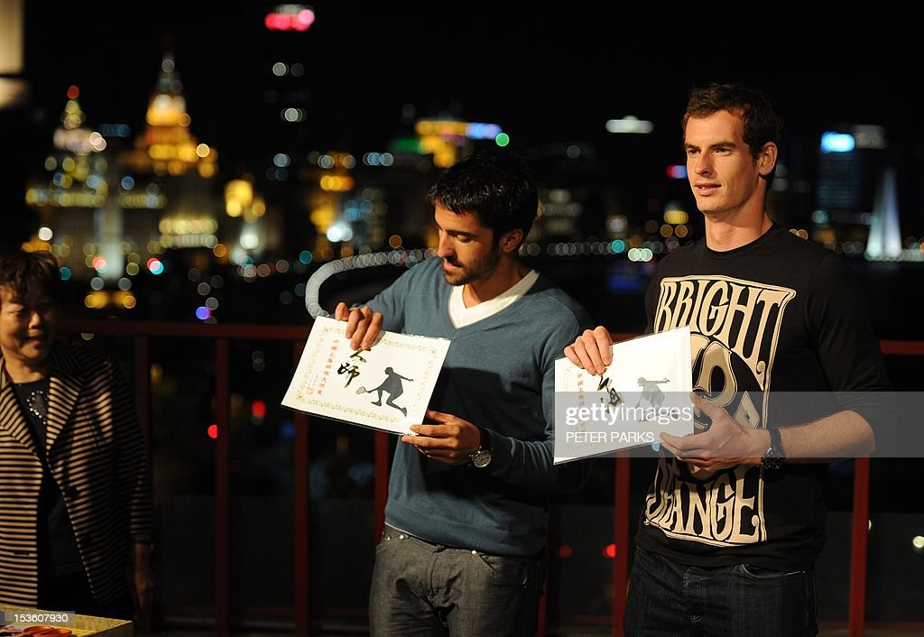 Andy Murray of Britain (R) and Janko Tipsarevic of Serbia (L) show traditional Chinese paper cuttings they did on a rooftop overlooking the Bund, at sponsors event ahead of the Shanghai Masters tennis tournament in Shanghai, on October 7, 2012. Murray can build on his breakthrough year by becoming the number one player in the world, top-ranked Swiss rival Roger Federer said at an earlier press conference. AFP PHOTO/Peter PARKS