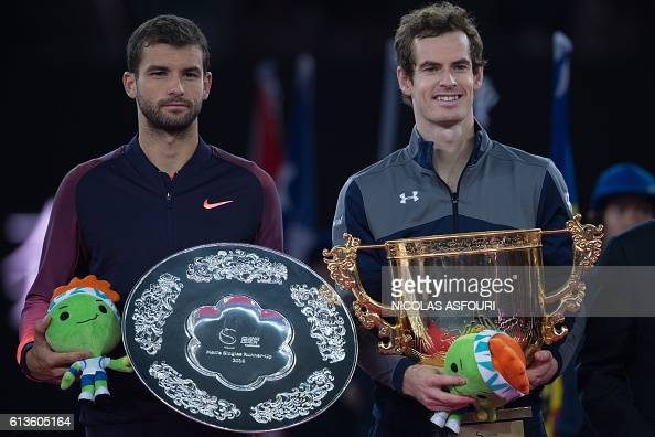 Andy Murray of Britain celebrates with the trophy as he wins against Grigor Dimitrov of Bulgaria in their men's singles final match of the China Open...