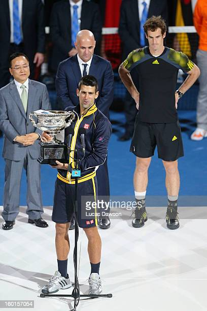 Andy Murray of Great Britain and Andre Agassi watch Novak Djokovic of Serbia hold the Norman Brookes Challenge Cup after Djokovic won their men's...