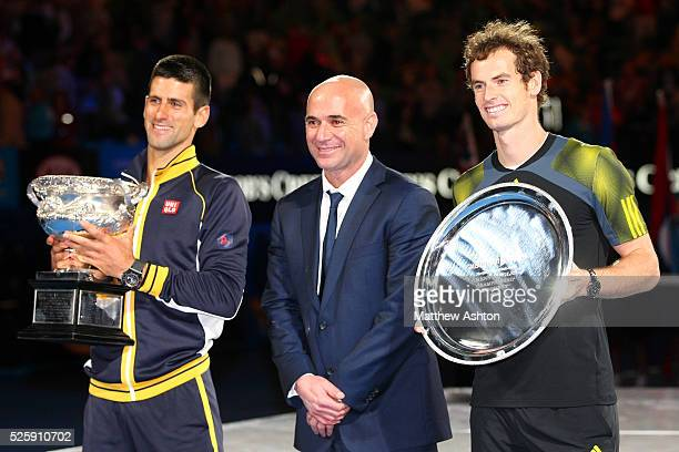 Andy Murray of Great Britain and Novak Djokovic of Serbia with Andre Agassi and the trophies during the Final at the Australian Open 2013