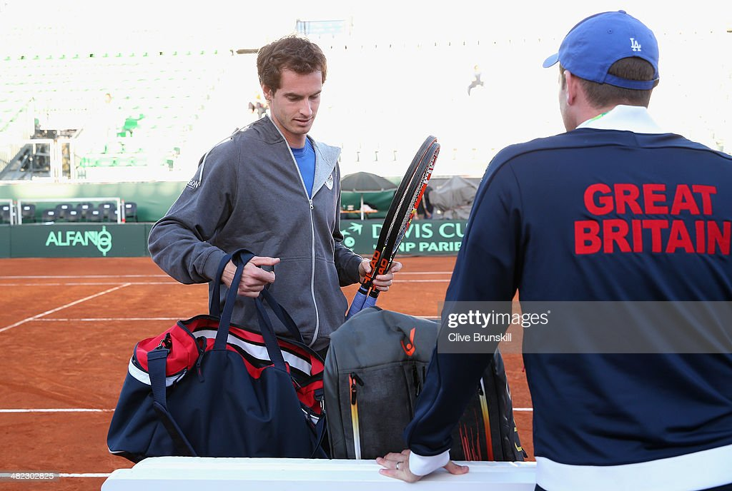 Andy Murray of Great Britain arrives on court for a late practice session watched by his team captain Leon Smith prior to the Davis Cup World Group Quarter Final match between Italy and Great Britain at Tennis Club Napoli on April 3, 2014 in Naples, Italy.