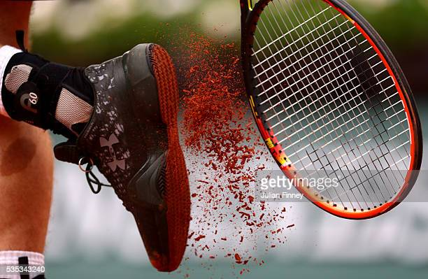 Andy Murray of Great Britain bangs clay from his shoes during the Men's Singles fourth round match against John Isner of the United States on day...