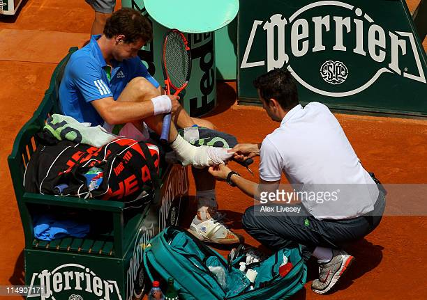 Andy Murray of Great Britain calls on the trainer for a second time to treat his injured foot during the men's singles round three match between Andy...